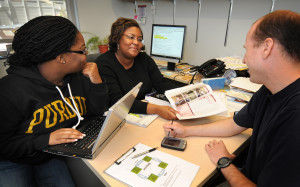 Monica Cox (at center), an assistant professor of engineering education, speaks with graduate students Tenille Medley and Nathan McNeill during a research meeting. Photo courtesy of Purdue University.